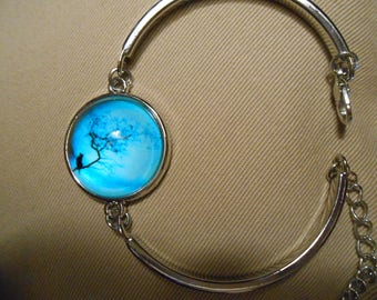 Black cat on a tree branch with a blue background bangle
