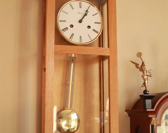 Very good condition wall Clock, fine model, in a gold colour pine case. Brass mechanism, shiny attractive pendulum, nice gong sound