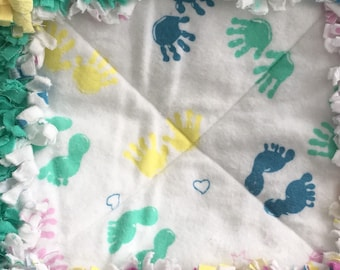 Little hands and feet with yellow, purple and sea green rag blanket