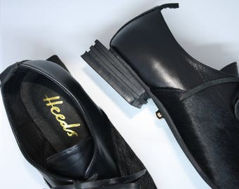 Modern designer shoe with an avante garde square rubber heel. Padded insole for maximum comfort.