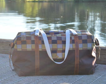 Large Rugged Oiled Canvas water and stain resistant travel duffel with leather trim and brass snap pockets