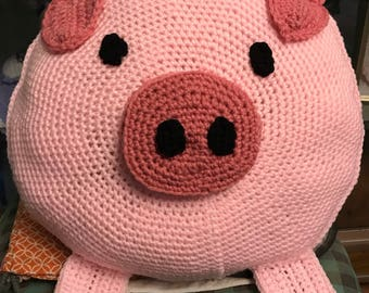 Crochet pig pillow with bow.