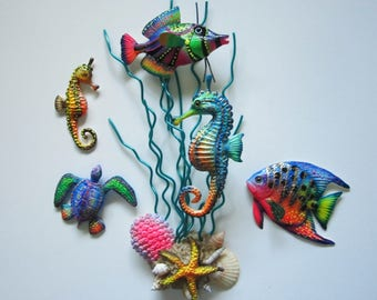 Colorful fish, seahorse art, turtle sculpture, marine life assemblage, beach wall decor