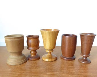 Five small turned wood cups, vases