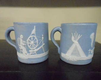 Pisgah Forest Pottery 1950 Cameo or Pate-Sur-Pate Pioneer Scene Spinning Wheel & Teepee Campfire Pair Blue w/White Mugs Signed Stephen