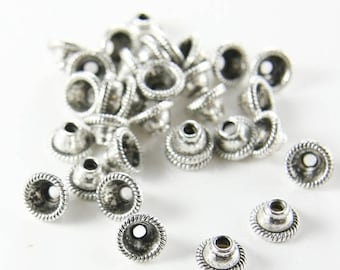 Beads sold u scalloped cone shape silver metal caps