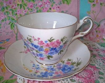 1950s Regency English bone china footed cup and saucer with pretty pink and blue flowers front and back and gold rim and on handle.