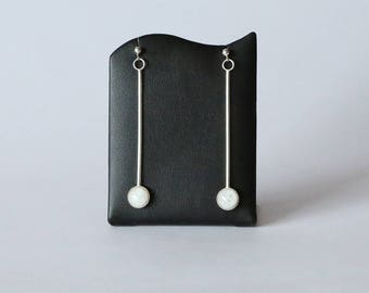 A pair of long, straight drop, sterling silver earrings. Set with ice white, kiln fired enamels. Hypoallergenic too! Free UK postage.