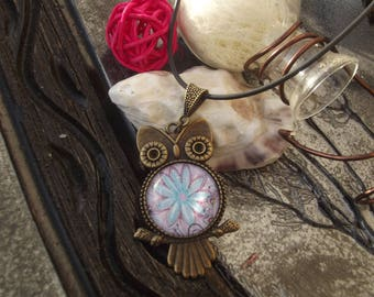 Large bronze OWL charm and necklace glass cabochon with blue flower on pink background and black leather cord.