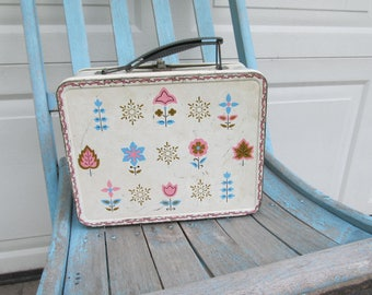 Vintage metal lunchbox with whimsical print, snowflakes and flowers in pink, blue, and brown