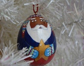 Black Santa wearing Navy blue shirt, Peruvian striped hat and mittens with gold star