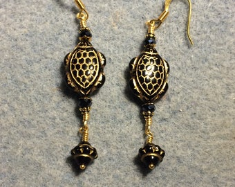 Black and gold Czech glass turtle bead earrings adorned with black Saturn beads and crystal beads.