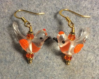 Clear and orange lampwork songbird bead dangle earrings adorned with orange Chinese crystal beads.