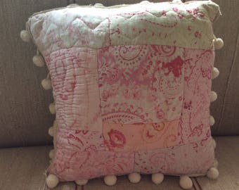 A sweet square cushion with vintage French quilt patchwork in a soft pink, red and cream Floral and Paisley Pattern.