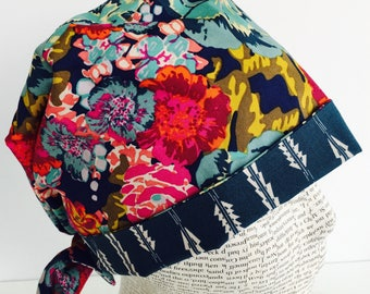 Tie Back Scrub Cap featuring a dark green material with flowers in teal pink and yellow with a coordinating band