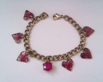 gold coloured bracelet with enamelled heart charms