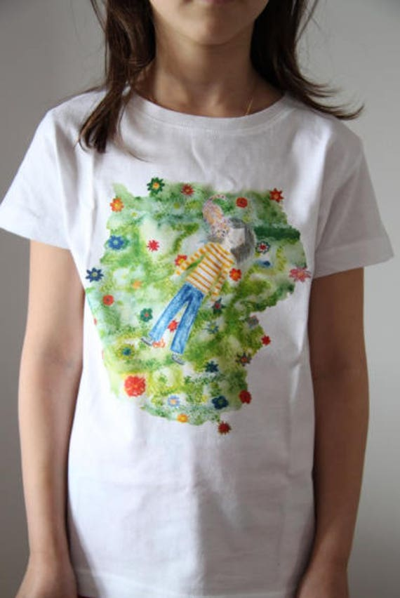 Graphic T-shirt kid little girl lying on the grass