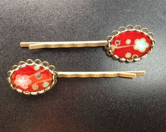 Hair clips, red paper with turquoise and pink flowers.