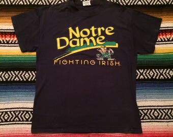 Vintage 90s Notre Dame Fighting Irish Spell Out Graphic T-Shirt by 20/20 Sport Sz M College 1990s Navy Blue Logo VTG