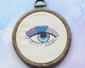 """Eye embroidery hoop art in 3"""" hoop. Home decor; embroidered art; Purple, lilac, and blue eyeshadow and iris"""