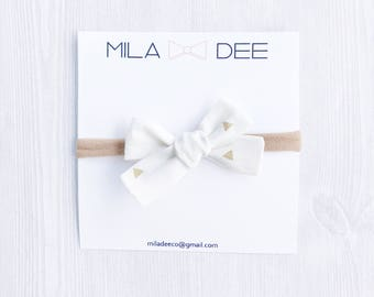 Ivory fabric bow with gold triangles on a nylon headband • baby headband • nylon headband • newborn headband • bow headband • ivory bow