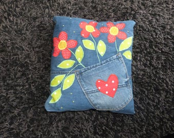 A denim pillow with flower patch