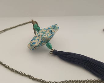 Silver tone necklace with an origami saucer with tassel