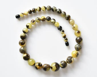 Beads of perfectly round form and green patterns