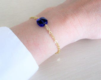 Golden brass chain strap and blue glass bead.
