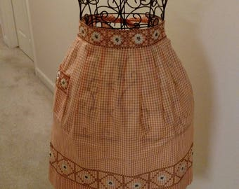 Vintage pre-owned and worn orange and white gingham party apron with cross-stitch
