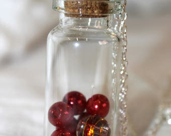 Necklace with glass flask with red beads