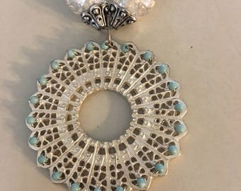 Silver and Turquoise necklace with a handcrafted charm. Great for any occasion to dress up any fashion!!