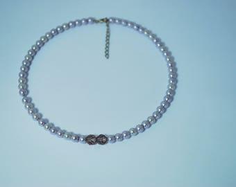 Support collier fausses perles mauve rigide