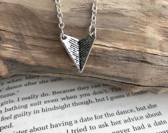 Arrowhead style silver necklace with a silver chain triangle paper aeroplane textured