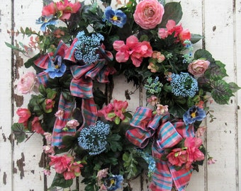 Spring Wreath with Dark Blue Pansy, Watermelon Asalea, Pink Ranunculus, Blue Queen Anne Lace, Light Pink Daisy and a Pink/Turq. Strip Bow