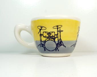 a 12oz cup painted in a color block of yellow & grey gray with Drumkit prints READY TO SHIP