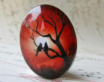 Lovebirds in a tree silhouette against a full moon, 40x30mm handmade glass oval cabochon, red sky, sunset, from our Mystic Moon collection