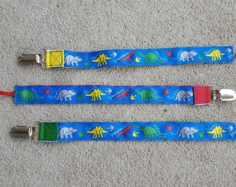 dinosaurs pacifier clips in primary colors