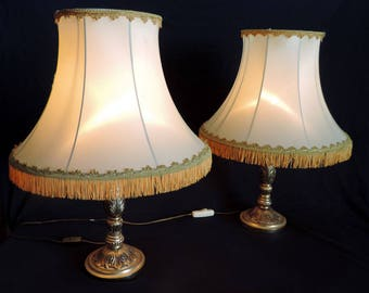 A pair of vintage French bronze table lamps with cream coloured lampshades