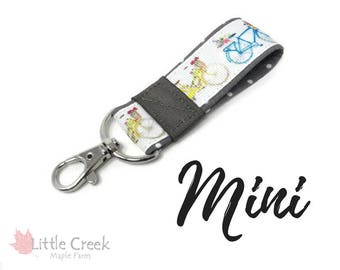 bicycle Mini key fob, yellow and blue bikes with flowers in the basket, old fashioned two wheeler on white and gray