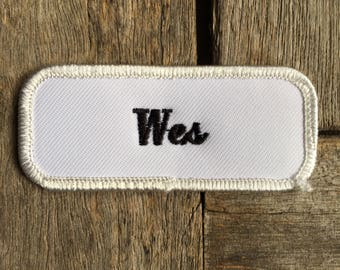 """Wes. A white work shirt name patch with """"Wes"""" in black print."""
