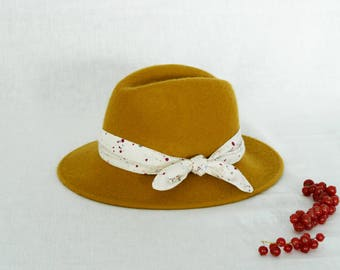 Mustard fedora hat decorated with a cotton scarf