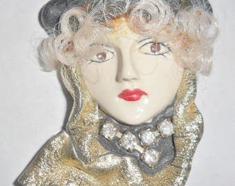 Beautiful vintage white lady woman face resin figural brooch with curly hair and black hat and gold colored scarf