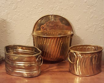 Trio of vintage brass planters.  Small planters, one oval, one diamond and one a wall planter.  Small vinage brass planters.