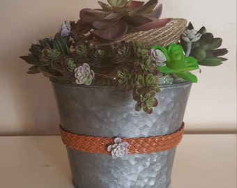 Assorted succulents in oval galvanized vase with burlp