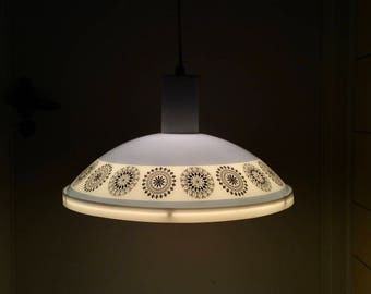 Mid-century modern baby blue UFO pendant light. Glass shade with modernist graphic décor of black circle filigree. White plastic diffusor.