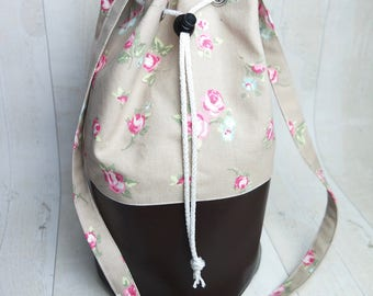 Draw string bucket handbag, made with faux leather and cotton fabric.