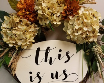 "18"" grapevine wreath decorated with artificial flowers and wooden sign saying ""this is us"""