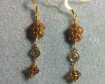 Marbled topaz Czech glass turtle bead dangle earrings adorned with gold swirly connectors and topaz Saturn beads.