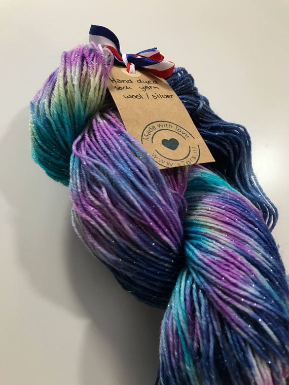 Hand dyed Merino sock yarn with a string of silver polyamide. Dyed in the colours of Nebula.